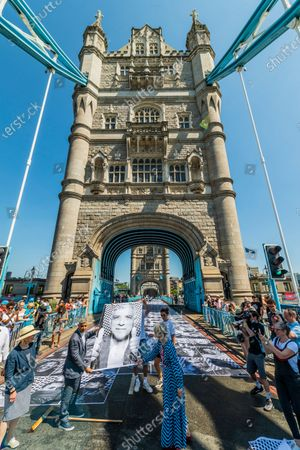 Sadiq Khan (pictured placing his picture on the bridge with Justine Simons, OBE, Dep Mayor for Culture) visits Tower bridge as it is pasted with more than 3,000 black and white portrait photographs in celebration of the UEFA EURO 2020 Football Championships. The Inside Out project has been created by artist JR's and will move on to cover pavements, roads and buildings across the city with his epic black and white portraits - including this gallery longer than two football pitches along the road at Tower Bridge. Inside Out is the capital's cultural celebration of football and its ability to bring people together.