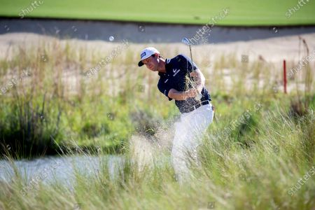 Stock Photo of Harris English hits out of the bunker on the 18th green during the final round of the Palmetto Championship golf tournament in Ridgeland, S.C