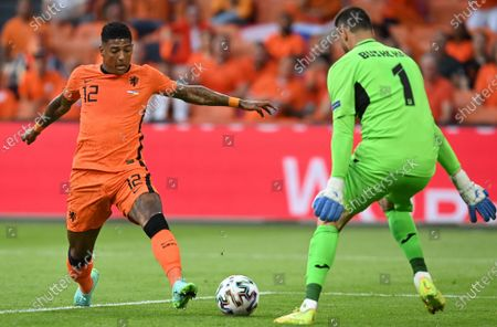 Patrick van Aanholt (L) of the Netherlands in action against goalkeeper Heorhiy Bushchan of Ukraine during the UEFA EURO 2020 preliminary round group C match between the Netherlands and Ukraine in Amsterdam, the Netherlands, 13 June 2021.
