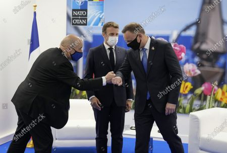 Stock Photo of French President Emmanuel Macron, center, and French Foreign Minister Jean-Yves Le Drian greet Poland's President Andrej Duda during a bilateral meeting on the sidelines of a NATO summit at NATO headquarters in Brussels, . U.S. President Joe Biden is taking part in his first NATO summit, where the 30-nation alliance hopes to reaffirm its unity and discuss increasingly tense relations with China and Russia, as the organization pulls its troops out after 18 years in Afghanistan