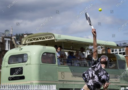People watch from the top of a double decker bus cafe as Reilly Opelka of the United States plays a return to John Millman of Australia during their singles tennis match at the Queens Club tournament in London