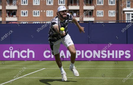 Reilly Opelka of the United States plays a return to John Millman of Australia during their singles tennis match at the Queens Club tournament in London