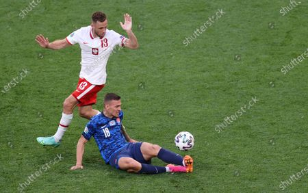 Poland's Maciej Rybus, left, challenges for the ball with Slovakia's Lukas Haraslin during the Euro 2020 soccer championship group E match between Poland and Slovakia at Gazprom arena stadium in St. Petersburg, Russia