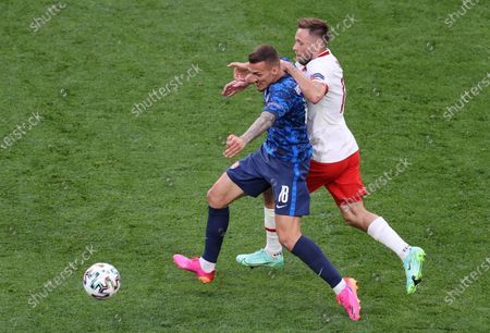 Maciej Rybus (R) of Poland in action against Lukas Haraslin of Slovakia during the UEFA EURO 2020 group E preliminary round soccer match between Poland and Slovakia in St. Petersburg, Russia, 14 June 2021.