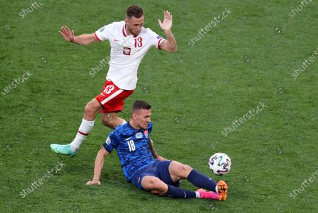 Maciej Rybus (L) of Poland in action against Lukas Haraslin of Slovakia during the UEFA EURO 2020 group E preliminary round soccer match between Poland and Slovakia in St. Petersburg, Russia, 14 June 2021.