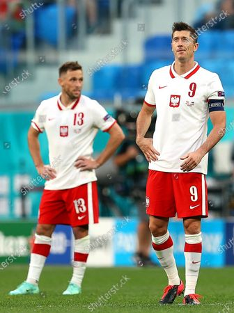 Polish players Maciej Rybus (L) and Robert Lewandowski (R) react during the UEFA EURO 2020 group E preliminary round soccer match between Poland and Slovakia in St. Petersburg, Russia, 14 June 2021.
