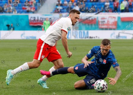 Slovakia's Lukas Haraslin, right, duels for the ball with Poland's Maciej Rybus during the Euro 2020 soccer championship group E match between Poland v Slovakia at the Saint Petersburg stadium in St. Petersburg, Russia