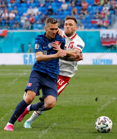 Slovakia's Lukas Haraslin, left, duels for the ball with Poland's Maciej Rybus during the Euro 2020 soccer championship group E match between Poland v Slovakia at the Saint Petersburg stadium in St. Petersburg, Russia