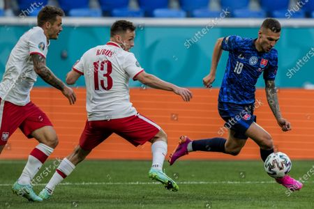 Slovakia's Lukas Haraslin, right, duels for the ball with Poland's Maciej Rybus, center, during the Euro 2020 soccer championship group E match between Poland and Slovakia at the Saint Petersburg stadium in St. Petersburg