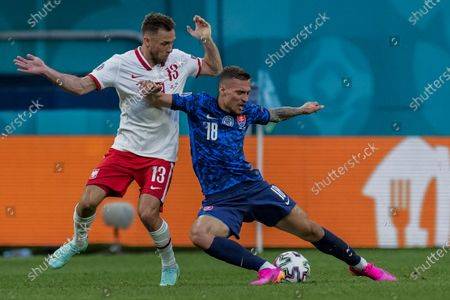 Poland's Maciej Rybus, left, duels for the ball with Slovakia's Lukas Haraslin during the Euro 2020 soccer championship group E match between Poland and Slovakia at the Saint Petersburg stadium in St. Petersburg