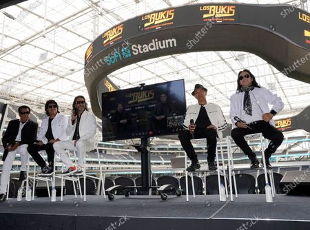 """Members of the Mexican grupera band Los Bukis, from left, Pedro Sanchez, Roberto Guadarrama, Marco Antonio Solis, on screen Joel Solis and Pepe Guadarrama, and Eusebio """"El Chivo"""" Cortez and Jose Javier Solis attend a press conference at SoFi Stadium, in Inglewood, Calif. Twenty five years after their last show as a band, the group announced that they are reuniting for a U.S. tour"""