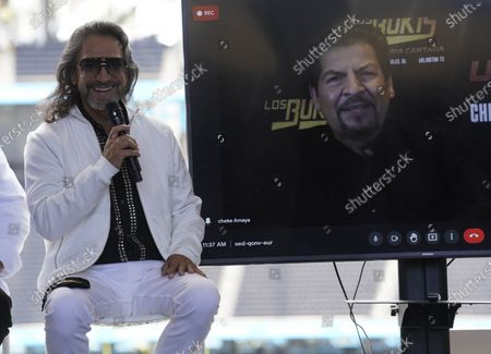 Members of the Mexican grupera band Los Bukis, Marco Antonio Solis, left, and Joel Solis, on screen, attend a press conference at SoFi Stadium, in Inglewood, Calif. Twenty five years after their last show as a band, the group announced that they are reuniting for a U.S. tour