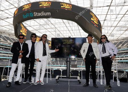 """Stock Picture of Members of the Mexican grupera band Los Bukis, from left, Pedro Sanchez, Roberto Guadarrama, Marco Antonio Solis, on screen Joel Solis and Pepe Guadarrama, and Eusebio """"El Chivo"""" Cortez and Jose Javier Solis attend a press conference at SoFi Stadium, in Inglewood, Calif. Twenty five years after their last show as a band, the group announced that they are reuniting for a U.S. tour"""