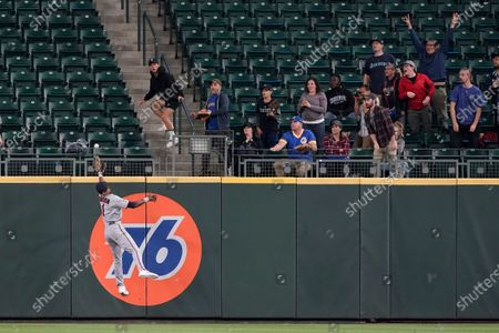 Seattle Mariners fans react as Minnesota Twins center fielder Nick Gordon leaps but can't catch a go-head solo home run hit by Seattle Mariners' Jake Bauers during the eighth inning of a baseball game, in Seattle