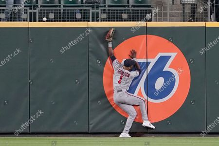 Minnesota Twins center fielder Nick Gordon leaps but can't catch a go-head solo home run hit by Seattle Mariners' Jake Bauers during the eighth inning of a baseball game, in Seattle. The Mariners won 4-3