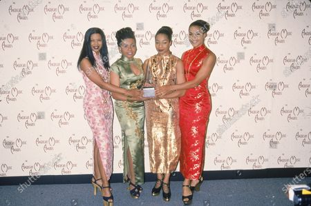 Portrait of popular rhythm and blues vocal group En Vogue, as they pose with an award trophy, backstage at the American Music Award ceremony, Los Angeles, California, January 25, 1993. From left, American singers Dawn Robinson, Maxine Jones, Terry Ellis, and Cindy Herron.