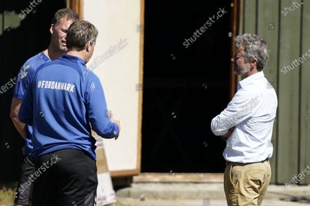 Crown Prince Frederik of Denmark (R) greets head coach for the Danish national soccer team Kasper Hjulmand (L) and his assistant Coach Morten Wieghorst (L-back) prior to the national teams training session, at Helsingoer Stadium, Denmark, 15 June 2021. Denmark will face Belgium on 17 June 2021 in group B of EURO2020.