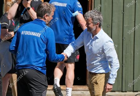 Crown Prince Frederik of Denmark, right, shakes hands with Denmark's manager Kasper Hjulmand, left, during a training session of Denmark's national team in Helsingor, Denmark, . It is the second training of the Danish team since the Euro championship soccer match against Finland when Christian Eriksen collapsed last Saturday