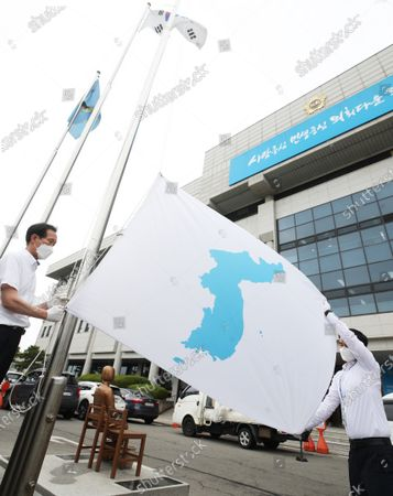 Employees raise a Korean Unification flag, which depicts a blue silhouette of the Korean Peninsula on a white background, at the provincial assembly building in Suwon, Gyeonggi Province, south of Seoul, South Korea, 15 June 2021, to mark the 21st anniversary of the first-ever inter-Korean summit held in June 2000 between then South Korean President Kim Dae-jung and North Korean leader Kim Jong-il.
