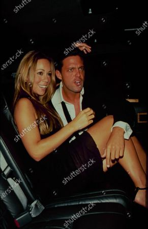 Stock Photo of Singers Mariah Cary and Luis Miguel sit together in the backseat of a limousine, New York, New York, June 15, 1999.