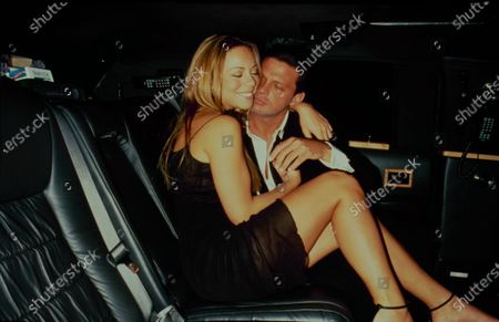 Stock Image of Singers Mariah Cary and Luis Miguel sit together in the backseat of a limousine, New York, New York, June 15, 1999.