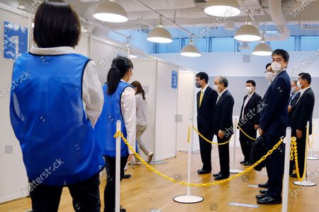 Stock Image of Covid 19 Vaccine Minister Taro Kono, center left, and Masayoshi Son, chief executive of technology company SoftBank Group Corp., center right, visit an inoculation site set up by Japanese technology company SoftBank Group Corp. at a WeWork office, in Tokyo. Japanese companies have joined the effort to speed up the country's lagging coronavirus vaccine rollout before the Tokyo Olympics begin next month