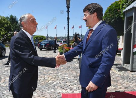 Portugal's President Marcelo Rebelo de Sousa (L) shakes hands with his Hungarian counterpart Janos Ader (R), in front of the presidential Alexander Palace in Budapest, Hungary, 15 June 2021.