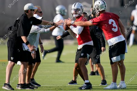 Las Vegas Raiders quarterback Marcus Mariota, center, takes part in a drill during an NFL football practice, in Henderson, Nev