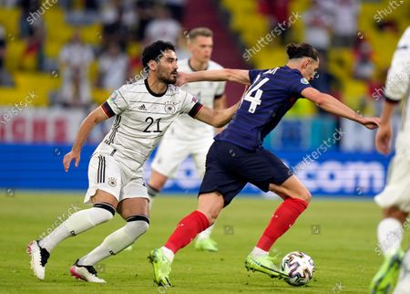 Germany's Ilkay Gundogan, left, battles for the ball with France's Adrien Rabiot during the Euro 2020 soccer championship group F match between France and Germany at the Allianz Arena in Munich, Germany