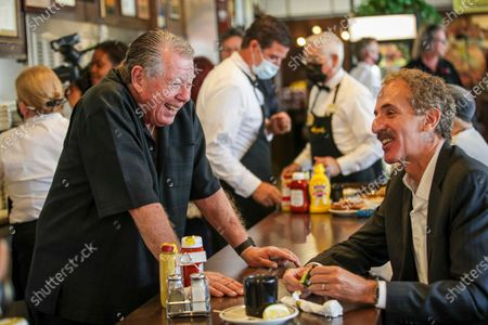 Stock Picture of Norm Langer, left, owner of Langer's Delicatessen-Restaurant , chats with City Attorney Mike Feuer at the reopening of the restaurant. Langer's Delicatessen-Restaurant be re-opened for the first time in over a year for in-person dining with new COVID-19 prevention guidelines for guest, according to contact. Langer's Delicatessen-Restaurant on Tuesday, June 15, 2021 in Los Angeles, CA. (Irfan Khan / Los Angeles Times)