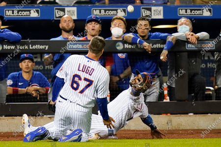 Chicago Cubs watch as New York Mets' Jonathan Villar, right, and relief pitcher Seth Lugo attempt to catch a foul ball by Anthony Rizzo during the ninth inning of a baseball game, in New York