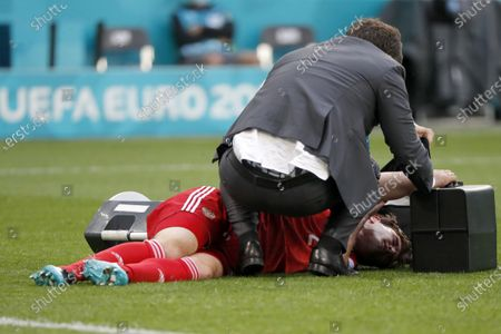 Russia's Mario Fernandes lays on the ground after his injuring during the Euro 2020 soccer championship group B match between Russia and Finland at the Saint Petersburg stadium, in St. Petersburg, Russia