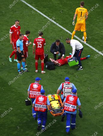 Mario Fernandes (bottom C) of Russia receives medical assistance during the UEFA EURO 2020 group B preliminary round soccer match between Finland and Russia in St.Petersburg, Russia, 16 June 2021.