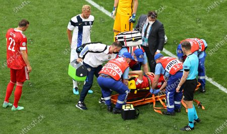 Mario Fernandes (C) of Russia is stretchered off the pitch after being injured during the UEFA EURO 2020 group B preliminary round soccer match between Finland and Russia in St.Petersburg, Russia, 16 June 2021.