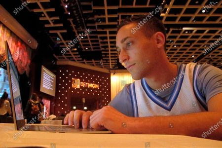 Stock Image of Jonathan Price, from the Staten Island borough of New York, researches picks for the NCAA college basketball tournament on March 19, 2021 at the Borgata casino in Atlantic City, N.J. On, a bill that would allow betting on New Jersey college teams, or teams from other states whose games are played in New Jersey, moved a step closer to approval