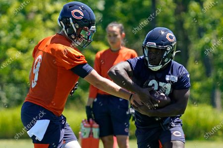 Chicago Bears quarterback Nick Foles, left, works running back CJ Marble during NFL football practice in Lake Forest, Ill