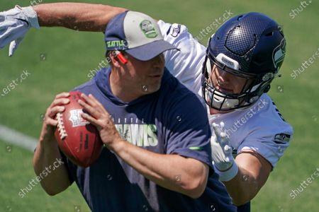 Stock Image of Seattle Seahawks linebacker Ben Burr-Kirven runs a drill with linebackers coach John Glenn, left, during NFL football practice, in Renton, Wash
