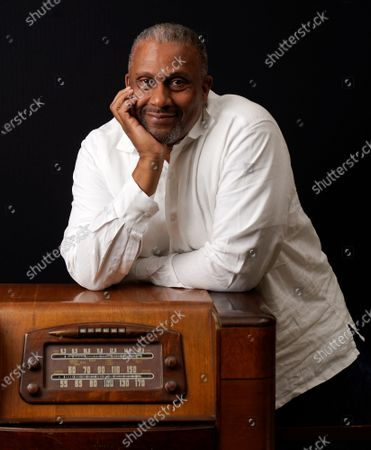 Stock Picture of Tavis Smiley, owner of progressive talk radio station KBLA Los Angeles (1580), poses for a portrait on a vintage AM radio in his station's offices, in Los Angeles. KBLA's morning drive host Dominique DiPrima gifted Smiley with the radio in celebration of the radio station's launch