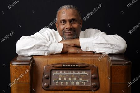 Stock Image of Tavis Smiley, owner of progressive talk radio station KBLA Los Angeles (1580), poses for a portrait on a vintage AM radio in his station's offices, in Los Angeles. KBLA's morning drive host Dominique DiPrima gifted Smiley with the radio in celebration of the radio station's launch