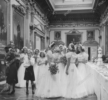 UNITED KINGDOM - JULY 01:  At the wedding of Raine McCorquodale to Gerald Legge, bridesmaids talking to each other at the reception while Ian Mccorquodale (L) stands by.