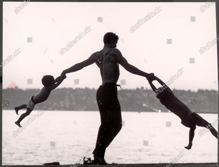 Stock Image of Silhouette of bare-chested ballet dancer Jacque d'Amboise w. his sons Christopher, 3, & George, 6, each respectively clinging to one of his hands as he swings them out around his body like a windmill on shore overlooking a lake while on vacation.