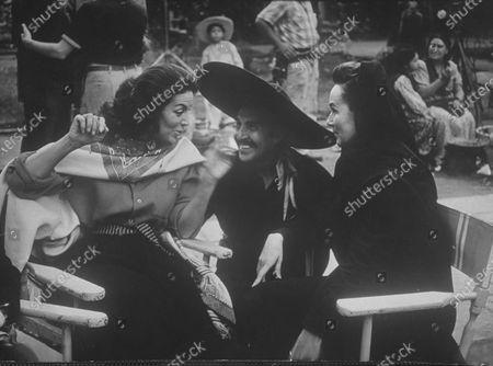 Actors Maria Felix (L), Indio Fernandez and Dolores del Rio (R) talking together during the filming of the movie La Cucaracha.