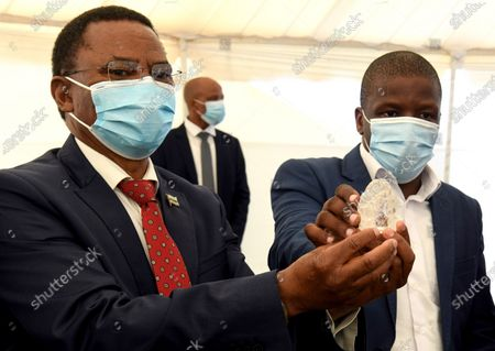 Botswana Vice President Slumber Tsogwane (L) holds a 1098 carat gem diamond unearthed by the Botswana Government and De Beers joint venture mining company Debswana, as it's being displayer at the Botswana State House to show to the President of Botswana Mokgweetsi Masisi, in Gaborone, Botswana, 16 June 2021 (Issued 17 June 2021). The stone measuring 73 by 52 by 27mm was found on 01 June 2021 and is the world's third largest of its kind according to Debswana mines.