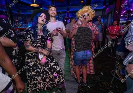 """Left to right-Molly McIsaac and her roommate Alex Humphrey watch a karaoke performance as Jack Hall greets drag queen Nico Cervantes, stage name """"Borgia Bloom"""", inside The Boulevard, the only gay bar in Pasadena on the first night in over a year that it was open with no social distancing restrictions and the return of live entertainment. The bar only allowed in people who said they were vaccinated. (Mel Melcon / Los Angeles Times)"""