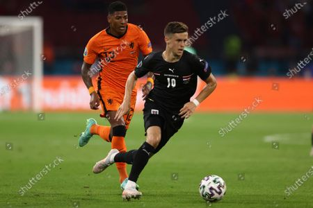 Patrick van Aanholt of the Netherlands, left, and Austria's Florian Grillitsch vie for the ball during the Euro 2020 soccer championship group C match between Netherlands and Austria at Johan Cruyff ArenA in Amsterdam, Netherlands