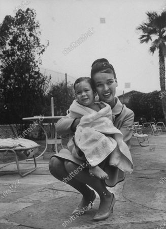2 year old, Mary Frances Crosby, daughter of Bing Crosby, after she won her Red Cross Merit Badge for beginner swimmers, with her mother.