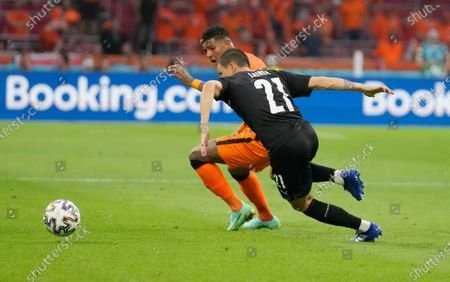 Patrick van Aanholt, left, of the Netherlands challenges for the ball with Austria's Stefan Lainer during the Euro 2020 soccer championship group C match between the The Netherlands and Austria at Johan Cruijff ArenA in Amsterdam, Netherlands