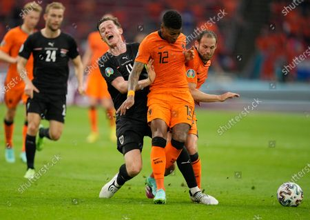 Austria's Michael Gregoritsch, left, challenges for the ball with Patrick van Aanholt, center, of the Netherlands and Daley Blind of the Netherlands during the Euro 2020 soccer championship group C match between the The Netherlands and Austria at Johan Cruijff ArenA in Amsterdam, Netherlands