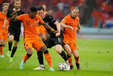Austria's Michael Gregoritsch, center, challenges for the ball with Patrick van Aanholt, left, of the Netherlands and Daley Blind of the Netherlands during the Euro 2020 soccer championship group C match between the The Netherlands and Austria at Johan Cruijff ArenA in Amsterdam, Netherlands