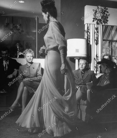 (L to R) John Fry, Lela Rogers, Benay Venuta and Joan Caulfield watching Angelita Scott (C) model an apricot chiffon tea gown.